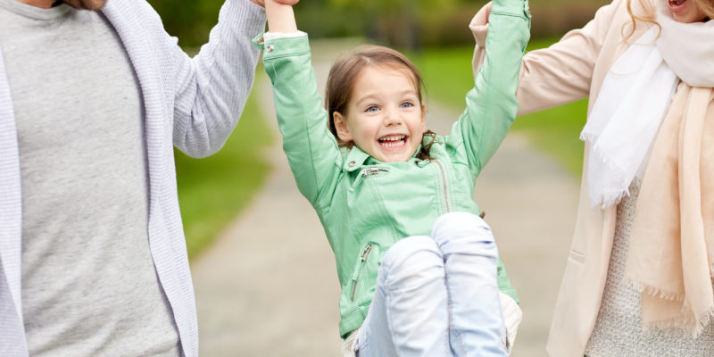 family, happiness, childhood and people concept - close up of happy mother, father and little girl walking in summer park and having fun